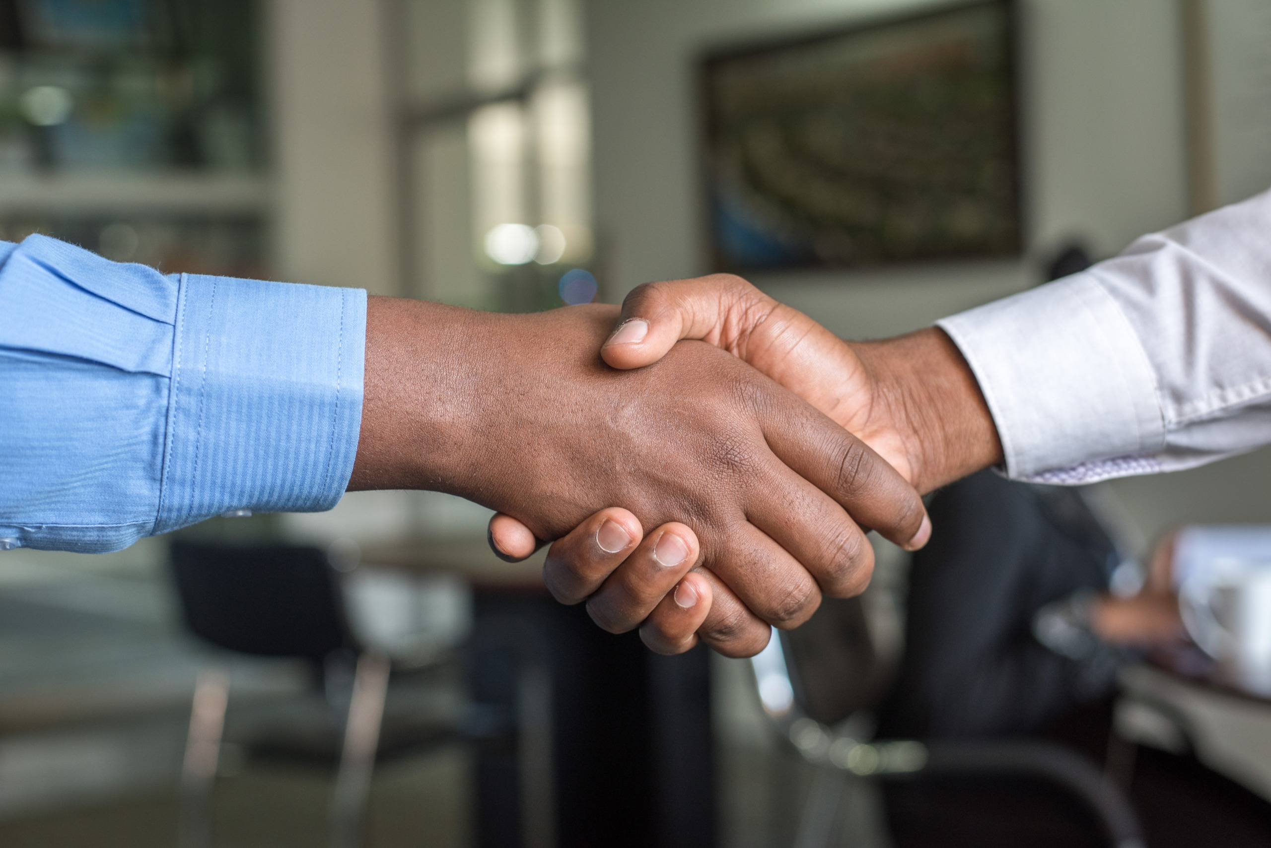 Recruitment agency staff shaking hands with a job candidate.